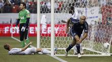 Sporting KC's Aurelien Collin (R) reacts after scoring against the Vancouver Whitecaps goalkeeper Joe Cannon (C) during the first half of their MLS soccer game in Vancouver, British Columbia April 18, 2012. (BEN NELMS/REUTERS)