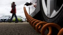 A man walks by an electric car plug during the Automobile Journalists Association of Canada's TestFest 2012 Canadian Car of the Year Awards in Niagara-on-the-Lake on Thursday, October 27, 2011. (Michelle Siu for AJAC) (Michelle Siu For The Globe and Mail)