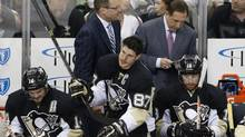 Pittsburgh Penguins' Chris Kunitz (14), Sidney Crosby (87), and James Neal (18) sit on the bench in front of coach Dan Bylsma, left rear, and assistant coach Jacques Martinin during the third period of Game 7 of a second-round NHL playoff hockey series against the New York Rangers in Pittsburgh on May 13. (AP)