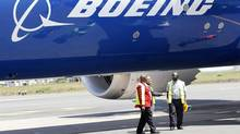 Engineers stand next to the Dreamliner 787-800 after its first landing at the Jomo Kenyatta airport in Nairobi. Boeing could engineer many ways to spoil Europe's $45-billion defence deal. (THOMAS MUKOYA/REUTERS)