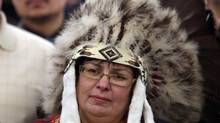 Attawapiskat Chief Theresa Spence, wearing a headdress, takes part in a drum ceremony before departing a Ottawa hotel to attend a ceremonial meeting at Rideau Hall with Gov. Gen. David Johnston in Ottawa Jan. 11, 2013. (FRED CHARTRAND/THE CANADIAN PRESS)