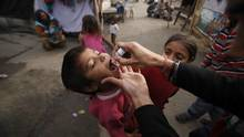 An Indian medical volunteer, right, administers a dose of Polio immunization to a child at a slum area in Jammu, India, Sunday, Feb.19, 2012. (Channi Anand/Associated Press)