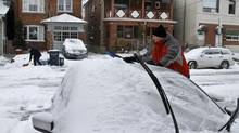 Toronto residents clear snow after a winter storm, Dec. 27 2012. (Fernando Morales/The Globe and Mail)