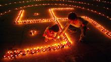 Children light lamps in the shape of Swastika, on the eve of Hindu festival of Diwali, in the northern city of Chandigarh, November 11, 2004. According to Hindu mythology, the swastika is the sign of prosperity. People decorate their homes with lights during the biggest Hindu festival of lights. (AJAY VERMA/Reuters)