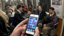 A commuter looks at his smart phone on the Metro in Montreal in this file photo. (Ryan Remiorz/THE CANADIAN PRESS)