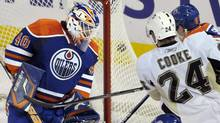 Edmonton Oilers' goalie Devan Dubnyk, left, watches the puck go into the net for a goal as Pittsburgh Penguins' Matt Cooke looks on during the third period of their NHL hockey game in Edmonton, January 14, 2010. (DAN RIEDLHUBER)