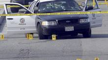 A bullet-damaged Los Angeles Police vehicle is taped off by police on Feb. 7, 2013, in Corona, Calif. Dorner is suspected of the shooting of two LAPD officers who were sent to Corona to protect someone he threatened in a rambling online manifesto. (Nick Ut/AP)