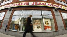A pedestrian walks past a Jean Coutu pharmacy in downtown Montreal. (SHAUN BEST/SHAUN BEST/REUTERS)