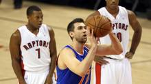 New York Knicks forward Andrea Bargnani (77) shoots a free throw as former teammates and Toronto Raptors point guard Kyle Lowry (7) and guard DeMar DeRozan (10) look on at Air Canada Centre. (Tom Szczerbowski/USA Today Sports)