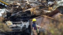 A firefighter walks past some piles of debris inside the red zone in Lac-Mégantic, Que., on July 14, 2013. (Peter Power/The Globe and Mail)
