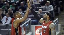 Miami Heat LeBron James (R) and teammate Chris Bosh (L) high five each other during the second half of their NBA basketball game against the Toronto Raptors in Toronto, March 17, 2013. (AARON HARRIS/REUTERS)
