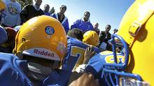 Images are for a feature on the Argos Level the Playing Field initiative that has helped bring back football programs to various high schools in the Toronto area. Sir Robert L. Borden, in blue and yellow, playing Lester B. Pearson C.I. in Scarborough (grey and black) is one of those schools. They are coached by Metro Toronto Police officers Martin Douglas, Jim Farrell, and a number of community coaches, and former student/player mentors. Coach Douglas, middle, speaking to the team before the game. (Peter Power/The Globe and Mail)