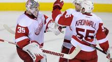 Detroit Red Wings' goalie Jimmy Howard, left, celebrates a 4-3 victory over the Calgary Flames with Jakub Kindl, centre, from Czech Republic, and Niklas Kronwall, from Sweden, after third period NHL action in Calgary, Alta., Friday, November 1, 2013. (LARRY MACDOUGAL/THE CANADIAN PRESS)