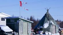 A tattered flag flies over a building in the impoverished first nations community of Attawapiskat. (Adrian Wyld/Adrian Wyld/THE CANADIAN PRESS)