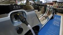 A man looks at an electric vehicle from Chinese automaker BYD during the opening day of the Shanghai Auto Show April 19, 2011. (CARLOS BARRIA/REUTERS/CARLOS BARRIA/REUTERS)