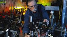"""In this 2003 photo provided by Geoffrey Wheeler and the National Institute of Standards and Technology, physicist David Wineland adjusts an ultraviolet laser beam used to manipulate ions in a high-vacuum apparatus containing an """"ion trap"""" used to demonstrate the basic operations required for a quantum computer. Wineland and Serge Haroche of France shared the 2012 Nobel Prize in physics Tuesday, Oct. 9, 2012 for inventing methods to observe the bizarre properties of the quantum world, research that has led to the construction of extremely precise clocks and helped scientists take the first steps toward building superfast computers. (Geoffrey Wheeler/AP)"""