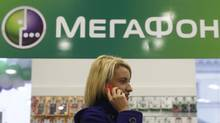 A customer speaks on her phone inside a MegaFon shop in St. Petersburg Nov. 15, 2012. Russia's No. 2 mobile phone operator wants to raise up to $2.3-billion (U.S.) from a planned share listing. (ALEXANDER DEMIANCHUK/REUTERS)