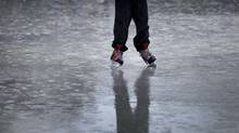 Warm weather and rain didn't keep some away from the soggy skating rink at Nathan Phillips Square in Toronto Dec 4, 2012. Toronto has had unusually high temperatures for early December, just weeks before the holidays. (Moe Doiron/The Globe and Mail)