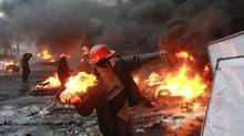 A pro-European protester throws a Molotov cocktail toward riot police near burning tires during clashes in Kiev. (GLEB GARANICH/REUTERS)