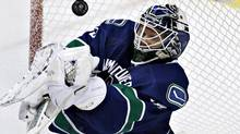 Vancouver Canucks goalie Cory Schneider deflects the puck during the third period of their NHL game against the Columbus Blue Jackets in Vancouver, British Columbia March 26, 2013. (ANDY CLARK/REUTERS)