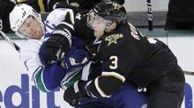 Vancouver Canucks centre Henrik Sedin is hit by Dallas Stars defenceman Stephane Robidas in the first period of a NHL hockey game in Dallas, Tex., February 1, 2011. (Reuters)