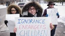 Pro-sex education demonstrators hold signs in front of Queen's Park in Toronto on Tuesday. (Darren Calabrese/The Canadian Press)