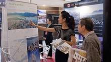 Angela Li, centre, pitches properties by Vancouver developer Westbank Corp. at a booth in Shanghai. From 2005 to 2012, nearly 37,000 millionaire migrants moved to B.C. under an investor program. (Kevin Lee For The Globe and Mail)
