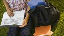 A student works on a laptop in the grass, surrounded by books. (iStockphoto)