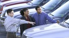 Salesman and couple car shopping. (Ron Chapple/Getty Images)