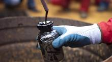 A worker collects a crude oil sample at a well operated by Venezuela's state oil company PDVSA. Global energy consumers are enjoying lower prices today but the plunge in crude costs – coupled with rising geopolitical tensions – is setting the stage for future supply shortages and price spikes, the International Energy Agency says in its annual World Energy Outlook. (CARLOS GARCIA RAWLINS/REUTERS)