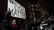 People protest a United States grand jury's decision not to indict a police officer who shot and killed Michael Brown of Feguson, Mo., outside the U.S. Consulate in Toronto on Tuesday, November 25, 2014. (THE CANADIAN PRESS)