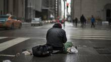 A man stays warm sitting over a grate on King Street West and Bay Street in Toronto on March 3 2016. (Fred Lum/The Globe and Mail)