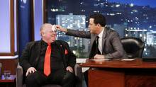 This March 3, 2014, image released by ABC shows Toronto Mayor Rob Ford, left, having his forehead wiped by host Jimmy Kimmel on the late night talk show Jimmy Kimmel Live in Los Angeles. (Randy Holmes/AP)