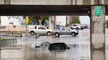 Cars sit in flood water after heavy rainfalls on Sunday, June 29, 2014 in Regina. (Liam Richards/THE CANADIAN PRESS)