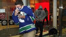 Vancouver Canucks fans loot merchandise through the smashed windows of a Sears store during a riot in reaction to their team's loss to the Boston Bruins in Game 7 of the NHL Stanley Cup final hockey game. (Reuters/Reuters)