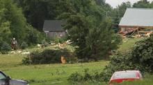 A fireman walks through a debris field off Goff Road in Smithfield follow a storm on Tuesday, July 8, 2014. (John Haeger/AP)