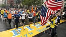 Runners who were unable to finish the Boston Marathon on April 15 because of the bombings cross the finish line on Boylston Street after the city allowed them to finish the last mile of the race in Boston, Saturday, May 25, 2013. (Winslow Townson/AP)