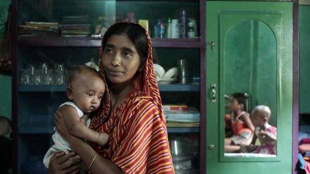 Garment factory worker Rahima holds her daughter Ritu Moni inside her slum house in Savar. Bangladesh's $19-billion garments industry attracts some of the world's biggest clothing brands because of low costs, but many retailers say unrest over pay and delayed shipping schedules are eroding that advantage. (ANDREW BIRAJ/REUTERS)