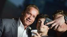 Arnold Schwarzenegger poses with fans at the Los Angeles premiere of Sabotage on Wednesday, March 19, 2014. (Richard Shotwell/Invision/AP)