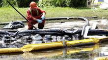 A worker monitors water in Talmadge Creek in Michigan after oil spilled from a ruptured pipeline, owned by Enbridge Inc., in July 2010. (Paul Sancya/The Associated Press)