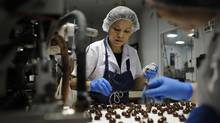 Workers in the Purdy's Chocolate factory in Vancouver, B.C. add a handmade letter 'c' on top of cherry chocolates. (Lindsay Mackenzie/Lindsay Mackenzie)