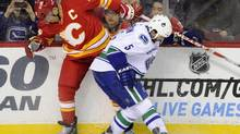 Vancouver Canucks' Jason Garrison, right, battles with Calgary Flames' Jarome Iginla during second period NHL action in Calgary on Sunday, March 3, 2013. (Larry MacDougal/THE CANADIAN PRESS)