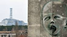 Graffiti is pictured on a wall in the ghost city of Pripyat near the fourth nuclear reactor (background) at the former Chernobyl Nuclear power plant, site of the world's worst nuclear disaster, on April 4, 2011. (SERGEI SUPINSKY/SERGEI SUPINSKY/AFP/Getty Images)
