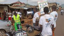 In this photo taken on Monday, Aug. 4, 2014, health workers speak to people on the streets to educate them about the deadly Ebola virus in the city of Freetown, Sierra Leone. Much of Africa's economy is taking a hammering from the Ebola crisis, and the damage is continuing to rise. (Youssouf Bah/AP)