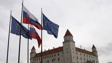 Flags of Slovakia and the European Union blow in the wind in front of the parliament building (Petr David Josek)
