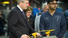 Prime Minister Stephen Harper, left, operates a plate roller as Diane Finley, Minister of Human Rseources and Skills Development, and worker Sunil Bagga look on during a visit to the Brannon Steel plant in Brampton, Ont. (Kevin Van Paassen/The Globe and Mail)