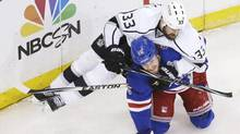 Los Angeles Kings defenceman Willie Mitchell falls on New York Rangers right wing Derek Dorsett in the third period during Game 4 of the NHL hockey Stanley Cup Final, Wednesday, June 11, 2014, in New York. (Associated Press)