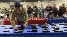 Handguns are shown at a gun auction in the United States. (Elisha Page/The Associated Press)