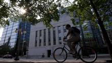 A cyclist passes the Bank of Canada in Ottawa. (Adrian Wyld/THE CANADIAN PRESS)