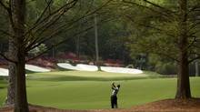Tiger Woods hits his approach shot to the 13th green during first-round play in the 2013 Masters tournament in Augusta, Ga., on Thursday. Woods, a heavy favourite, recorded a two-under 70 to sit in a tie for 13th, four shots off the lead. (MARK BLINCH/REUTERS)
